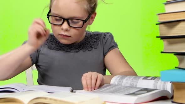 Thumbnail for Little Girl in Glasses Looking in Books Information. Green Screen