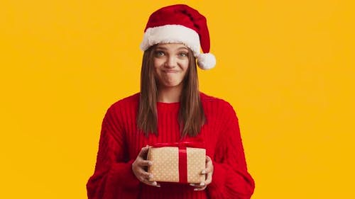 Young Displeased Woman in Santa Hat Holding Present Box and Frowning, Orange Studio Background