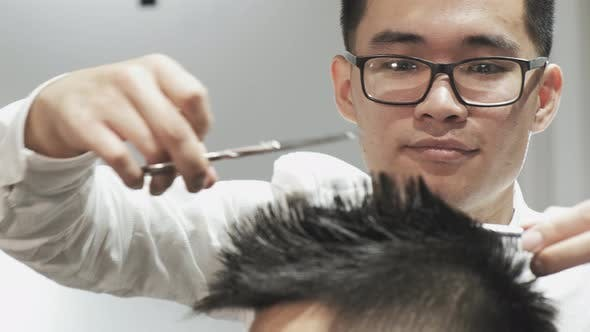 Thumbnail for Close-up of Male Hairdresser Hands Combing and Cutting Hair To Client in Salon.