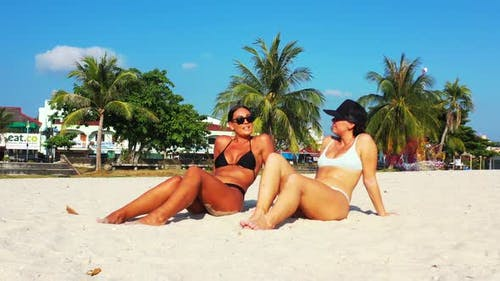 Young fun women travelling having fun on the beach on clean white sand and blue background