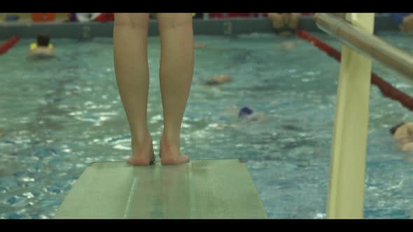 Thumbnail for Slow motion footage of high school swim team members at an indoor pool