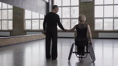 Couple of Dancers Holding Hands in Ballroom