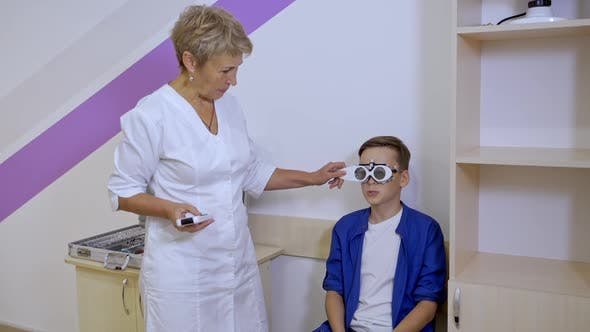 Ophthalmologist In Room With Boy. Shot of boy checking vision at eye clinic