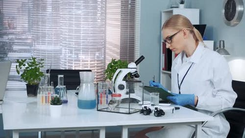 Smart Female Chemistry Scientist in Lab Coat Writing the Results of the Experiment