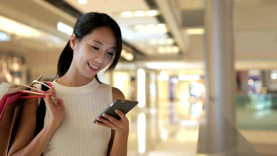Thumbnail for Woman using smart phone and holding paper bags in shopping mall