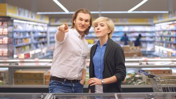 Thumbnail for Young Happy Couple in the Supermarket Choosing Products for a Family Celebration