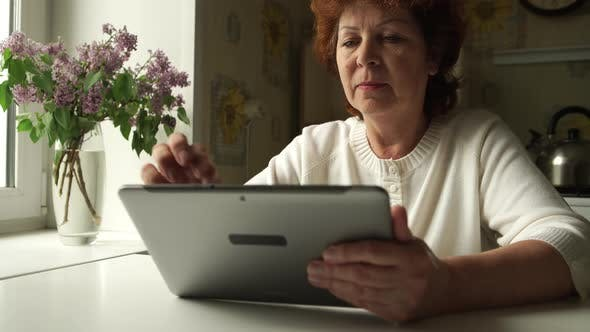 Thumbnail for Aged woman using a digital tablet PC at home