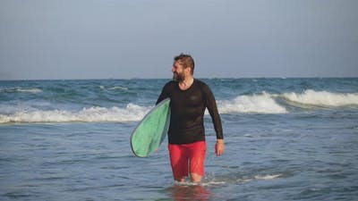 Portrait of a Handsome Senior Sportsman at the Age Carrying a Surfboard on the Beach