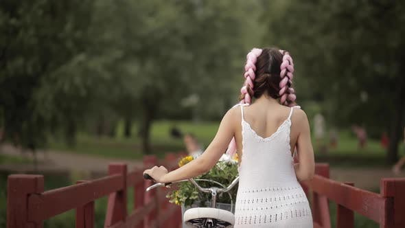 Thumbnail for View From Back of Girl in White Dress Riding Bicycle in Park
