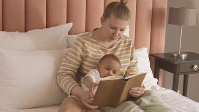 Mother Reading Book to Baby