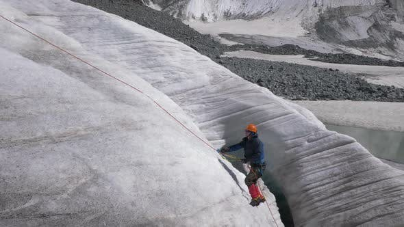 Cover Image for Mountaineer Man in Crampons Is Using Ascender on Fixed Rope on Steep Slope in Mountains