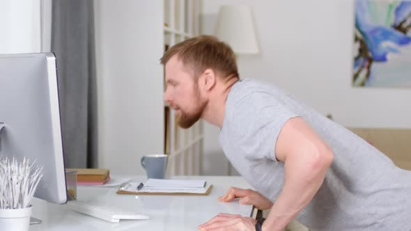 Thumbnail for Man Doing Table Push Ups and Watching Workout Video on Computer