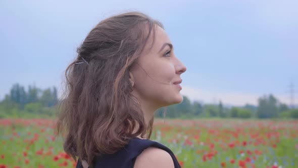 Thumbnail for Side View of a Pretty Girl in the Poppy Field Looking Away with a Happy Wide Smile