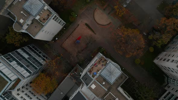 Scenic Top View Shot of a Ghetto Neighbourhood Backyard with Playground Slide in Between Apartment