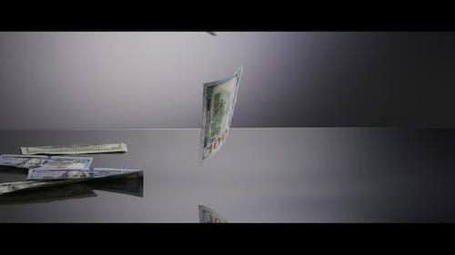 American $100 Bills Falling onto a Reflective Surface - MONEY 0035
