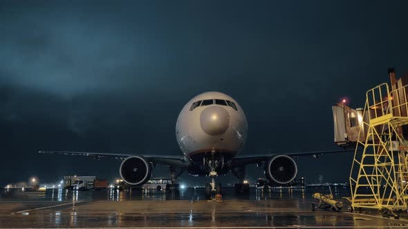 Cover Image for View To the Cockpit and Engines of Parked Airliner in Airport at Night