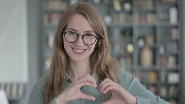 Portrait of Cheerful Young Woman Making Heart Shape with Hands
