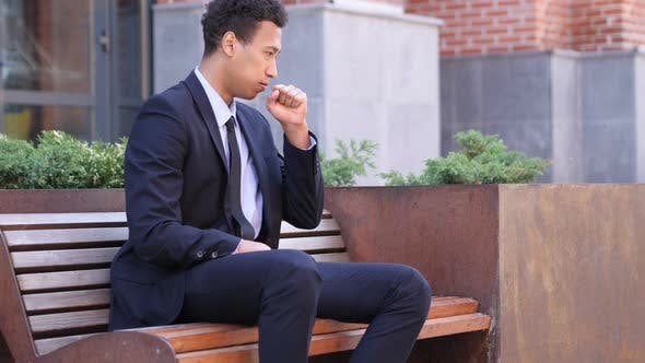 Thumbnail for Coughing African Businessman Sitting on Bench
