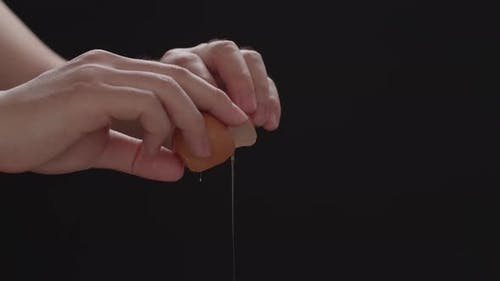 Hands Holding A Cracked Egg, Breaking An Egg