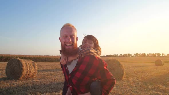 Joyful Dad Carrying Son Piggyback Running on Field