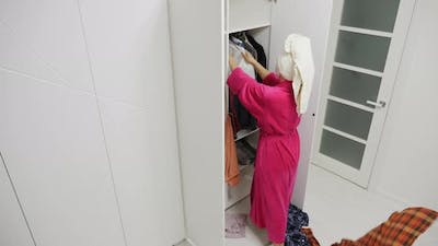 Annoyed Woman Throwing Clothes Out of the Closet