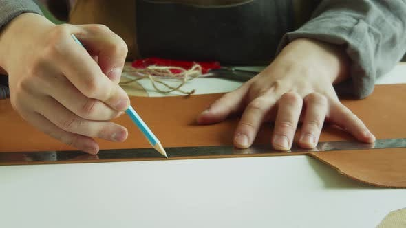 A Shoemaker Draws a Line with a Pencil on a Large Piece of Genuine Leather To Cut It Off. The