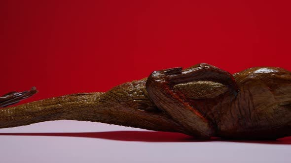 Thumbnail for A full smoked duck on a white surface with a red background