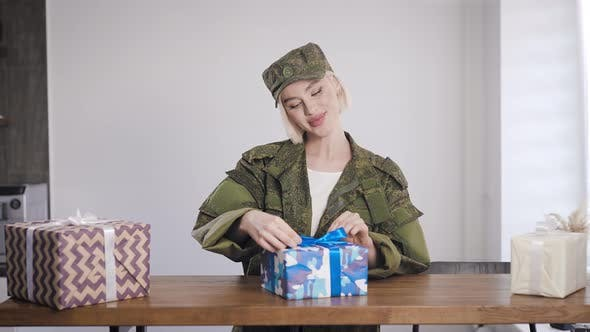 A Girl in Khaki Clothes Enjoys Gifts