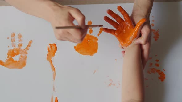 Mom Paints Children's Hands with Paints and the Child Puts a Handprint on the Paper