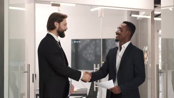Thumbnail for Two Smiling Businessmen Shaking Hands Together While Standing in an Office