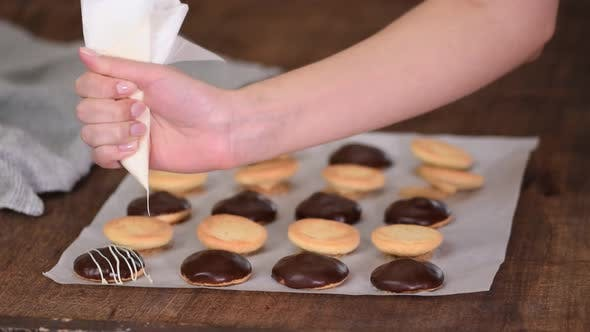 Female Chef Decorating Cookies with Melted Chocolate
