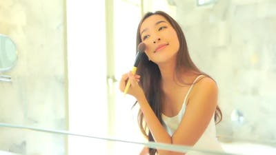 Young asian woman check her face on mirror