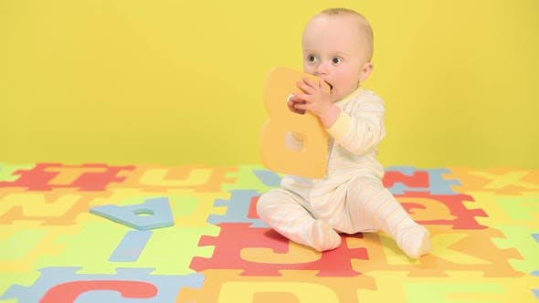 Thumbnail for Baby boy playing with toy alphabet letters
