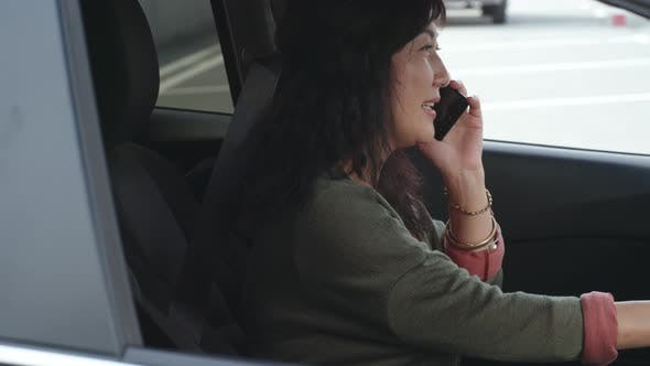 Cover Image for Asian Woman Sitting in Driver Seat and Talking on Phone
