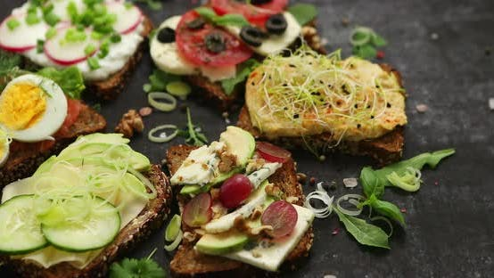 Variety of Healthy Fresh Sandwiches with Different Vegetables, Herbs and Ingredients on Dark Table