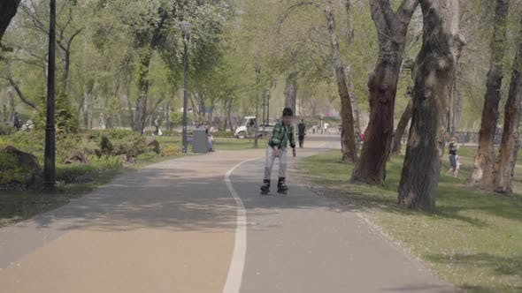 Thumbnail for Adorable Boy in Bright Clothes Rollerblading in the Park Near the River