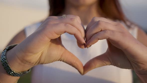 Thumbnail for Cropped Shot of Young Woman Making Heart Shape with Hands