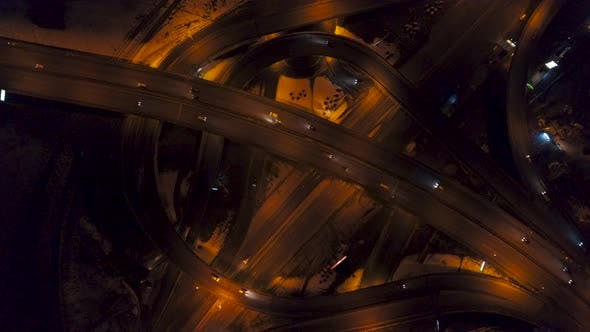 Vertical Top Down Aerial View of Traffic on Freeway Interchange at Night