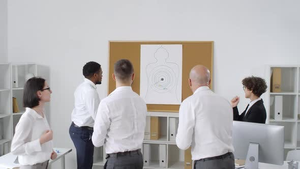 Cover Image for Office Workers Throwing Darts at Poster