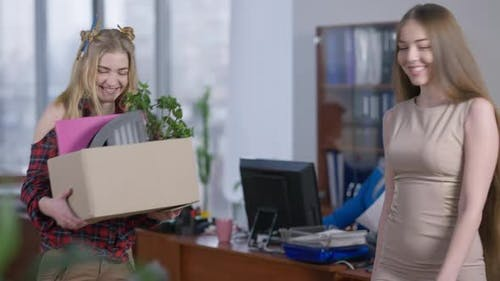 Positive Young Slim Woman Giving Box with Documents and Pot Flower to Happy New Employee