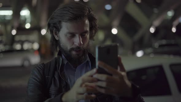 Thumbnail for Smiling Man Making Video Call on Smartphone in Night City