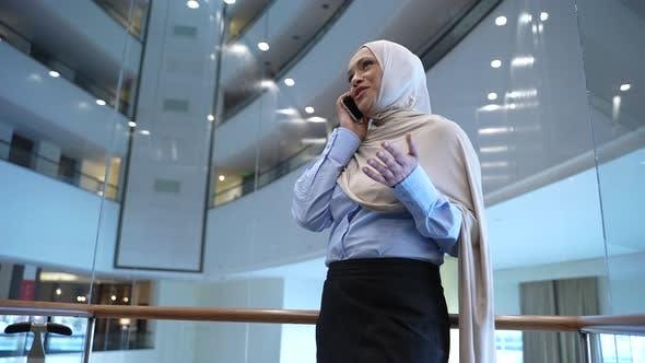 Joyful Muslim Woman Talking on Phone in Hotel Lift