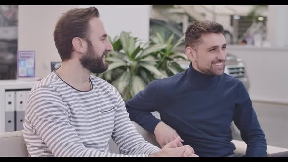 Thumbnail for Side View of Two Caucasian Handsome Men Sitting in Car Dealership, Smiling, and Talking