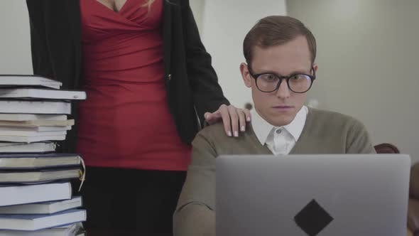 Thumbnail for Young Modestly Dressed Man in Glasses Sitting at Table at Home, Working on Laptop