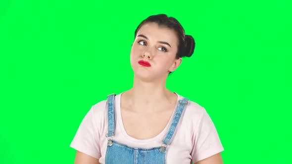 Thumbnail for Woman with Two Hair-buns Stands Waiting on a Green Screen. Slow Motion