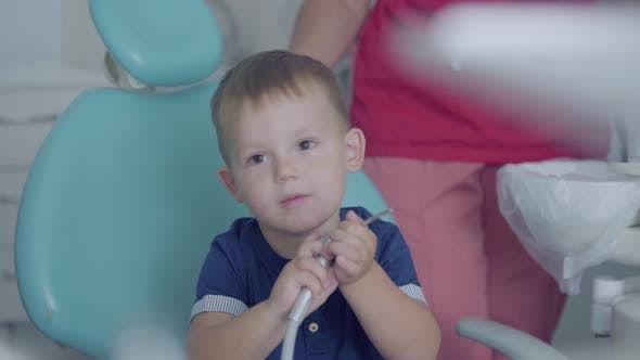 Thumbnail for Cute Little Boy Playing with Medical Tools Sitting in the Chair in the Dentist Office