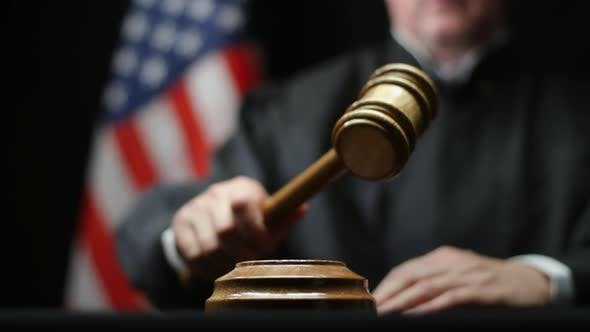 Cover Image for Judge's Hand Banging A Gavel On Block Against American Flag In United States Court