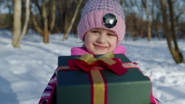 Joyful Little Smiling Kid Girl Holding Christmas Present Gift Box in Winter Park Xmas Eve Holidays