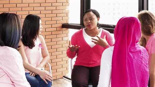 Women wearing pink color clothes sitting in circle talking in breast cancer awareness campaign