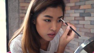 Asian Woman Painting Eyebrow